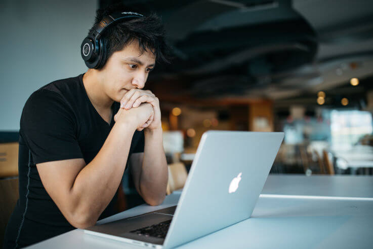 An intelligent insight on how to get out of your debts - Man listening to music at laptop