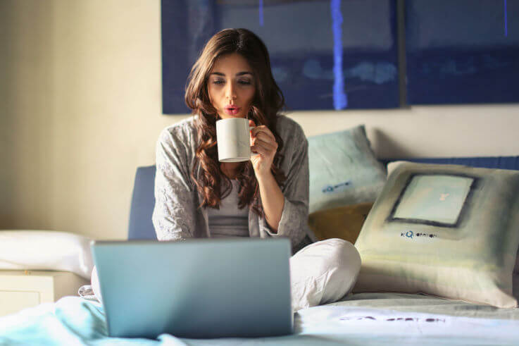 Debt help self employed pay off debt - Woman on laptop in bed
