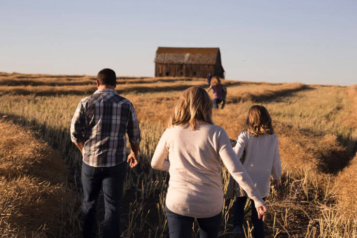 Guide to dealing with financial stress - Family walking through farmland