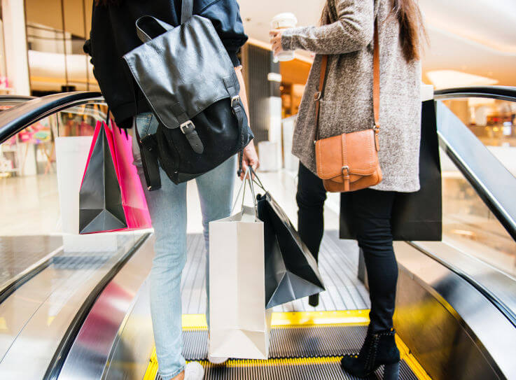 How to get rid of credit card debt - Women with shopping bags on escalator